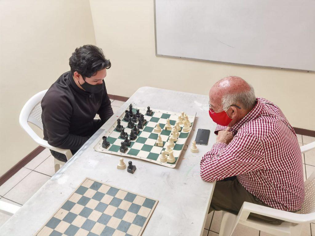 Dos hombres juegan ajedrez en una mesa