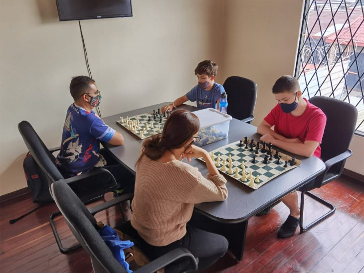 4 personas en una mesa jugando ajedrez
