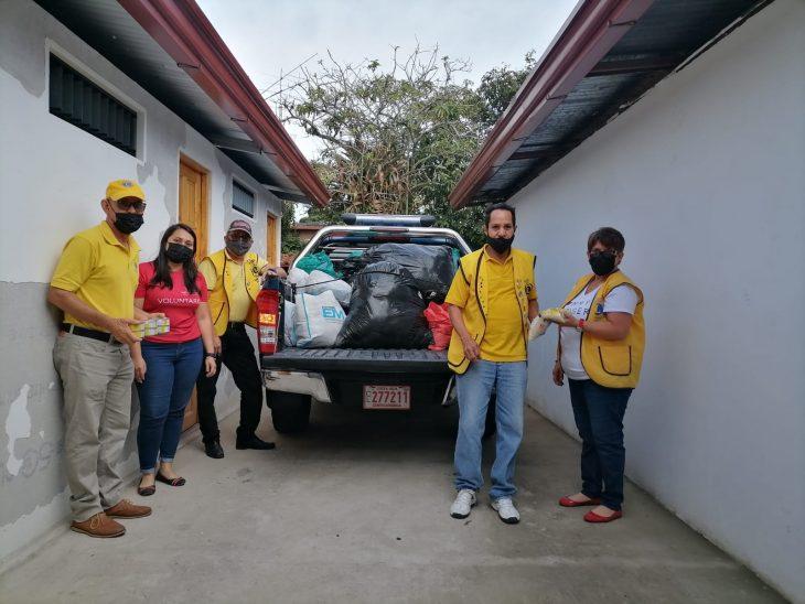 voluntarios bajan víveres de un carro